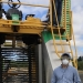 Wei Qiang Yang, Associate Professor and berry Extension agent for Oregon State University Extension Service, standing next to a blueberry harvesting machine.